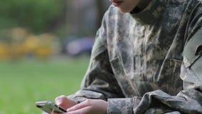 Soldado que manda un SMS en el teléfono almacen de metraje de vídeo