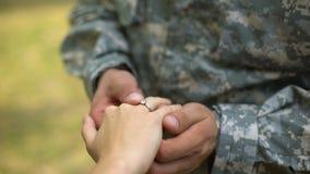 Soldado que põe a aliança de casamento sobre a mão das amigas, momento romântico, acoplamento video estoque