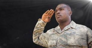 Soldado que saluda contra fondo negro con la capa y la llamarada del grunge Imagen de archivo