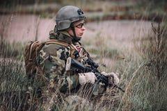 Soldado que se sienta en alta hierba en el campo imágenes de archivo libres de regalías