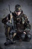 Soldado que se sienta en el piso Imagenes de archivo