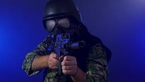 Soldado que sostiene el rifle de asalto en neblina ahumada almacen de video