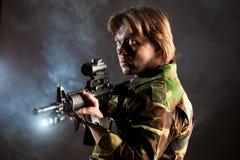 Soldado que sostiene un arma Imagen de archivo libre de regalías