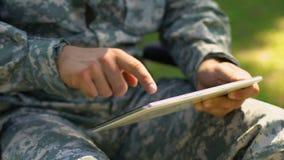 Soldado que usa la tableta al aire libre, servicio de asistencia psicológico en línea para los veteranos almacen de video