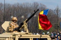 Soldado rumano del desfile del día nacional que saluda con la bandera rumana en el fondo fotografía de archivo