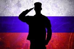 Soldado ruso orgulloso en el fondo ruso de la bandera Foto de archivo