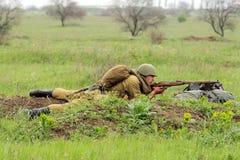 Soldado soviético del shooting WW2 en el campo Imagenes de archivo