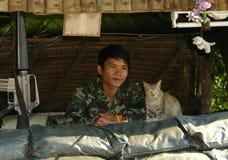 Soldado tailandés y gato que guardan junto en Roadbloc Imagen de archivo libre de regalías