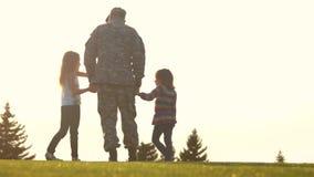 Soldado trasero de la visión que se coloca con dos pequeñas hijas metrajes