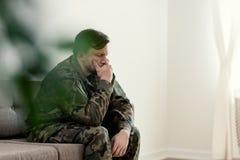 Soldado triste en el uniforme que cubre su boca mientras que se sienta en un sofá imagen de archivo