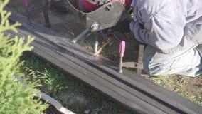 Soldador da soldadura do metal em um jardim privado Cerca feito a mão filme