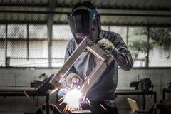 Soldador de trabalho na ação com faíscas brilhantes Fotografia de Stock