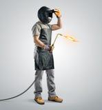 Soldador del trabajador en una máscara protectora con la máquina de la soldadura oxiacetilénica Fotografía de archivo