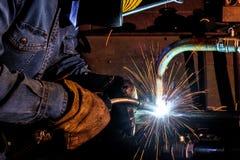 Soldador en las estructuras del metal de soldadura del trabajo fotografía de archivo libre de regalías
