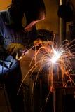 Soldador en las estructuras del metal de soldadura del trabajo foto de archivo