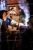 Soldador en las estructuras del metal de soldadura del trabajo imagen de archivo