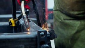 Soldador experimentado que lleva a cabo extremidad de la ventaja del arma de soldadura durante proceso de la soldadura metrajes