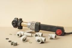 Soldador para los tubos plásticos para el abastecimiento de agua en la tabla de funcionamiento Accesorios para la construcción y  Foto de archivo libre de regalías