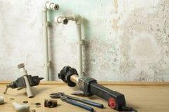 Soldador para los tubos y el equipo plásticos para sondear en la tabla de madera en viejo fondo de la pared Concepto de Repairmen imagen de archivo