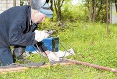 Soldador In Protective Clothing contratado al Ou de la construcción de la soldadura Foto de archivo libre de regalías