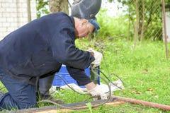 Soldador In Protective Clothing contratado a la construcción de la soldadura al aire libre en sitio Fotografía de archivo libre de regalías