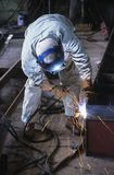 Soldador que dobra-se abaixo da soldadura no trabalho Foto de Stock Royalty Free