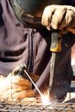 Soldador que suelda una pieza de metal Imagen de archivo libre de regalías