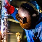 Soldador que trabaja en fábrica industrial fotos de archivo