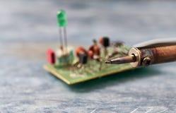 Soldador y componente electrónico en placa de circuito impresa imagenes de archivo