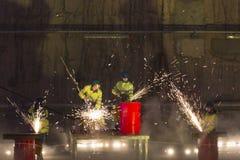 Soldadores na ação com as faíscas brilhantes durante a mostra da abertura de Foto de Stock Royalty Free