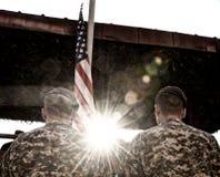 Soldados americanos y bandera de los E.E.U.U. con luz del sol fotografía de archivo