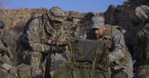 Soldados armados que olham um computador video estoque