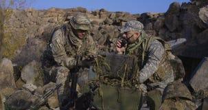 Soldados armados que olham um computador vídeos de arquivo