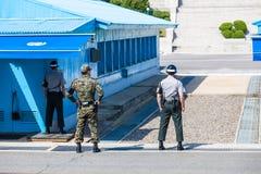 Soldados coreanos que olham a beira entre o sul e a Coreia do Norte na área comum da segurança (DMZ) fotografia de stock