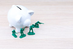 Soldados de brinquedo verdes na frente do mealheiro Fotos de Stock Royalty Free