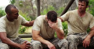 Soldados de Militray que consuelan a su compañero de equipo en el campo de bota 4k almacen de metraje de vídeo