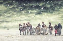 Soldados de Napoleon que marchan en nieve que cae con un cañón en la tierra llana, campo Foto de archivo