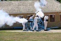 Soldados del siglo XIX que encienden el cañón Foto de archivo