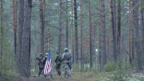 Soldados en camuflaje con las armas del combate y en los E.E.U.U. en el bosque, concepto militar almacen de video