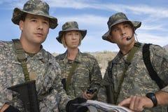 Soldados en el campo que mira el mapa Imágenes de archivo libres de regalías