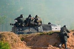 Soldados en un vehículo acorazado militar Imagenes de archivo