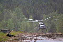 Soldados en una tierra fangosa con el helicóptero militar en el fondo - ejército y demostraciones de la tecnología militar Imagen de archivo libre de regalías