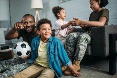 Soldados fêmeas e masculinos afro-americanos que jogam com suas crianças fotografia de stock royalty free