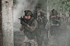 Soldados jovenes en patrulla en humo Imagen de archivo libre de regalías