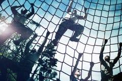 Soldados militares que escalam a corda durante o curso de obstáculo fotos de stock