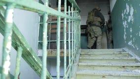 Soldados na camuflagem com a espreitadela das armas do combate ao longo dos corredores da construção velha, o conceito militar filme