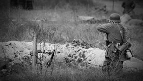 Soldados nazistas que disparam com um rifle e um almofariz na trincheira Filme velho do filme de WWII filme