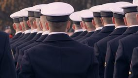 Soldados no uniforme azul e nos tampões bonitos brancos, guardando uma arma e uma posição em uma linha vídeos de arquivo