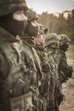 Soldados pesadamente en fila armados Fotos de archivo