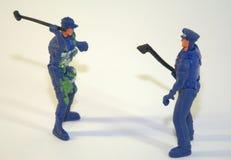 Soldados plásticos del ` s de los niños, dos figuras de policías en uniforme con la herramienta La imagen era primer admitido fotos de archivo
